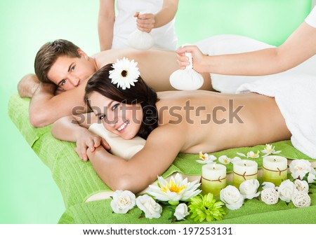 Portrait of smiling young couple receiving massage with herbal compress balls on back at beauty spa - stock photo