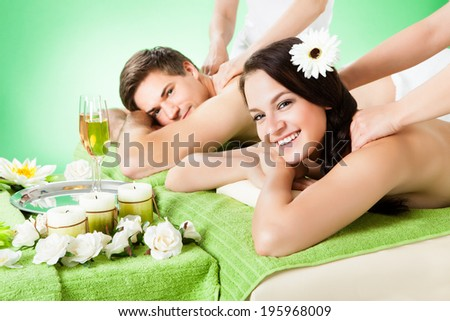 Portrait of smiling young couple receiving shoulder massage at beauty spa - stock photo