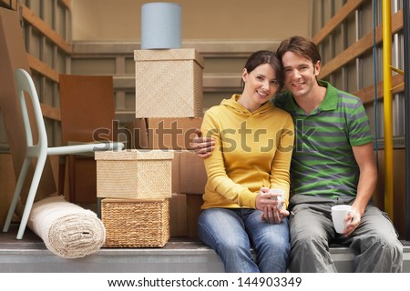 Portrait of smiling young couple sitting back of moving van - stock photo