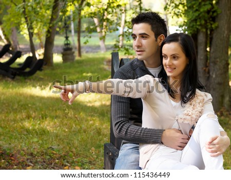 Portrait of smiling young couple sitting on a bench in park.Girl pointing to something with hand or finger. - stock photo