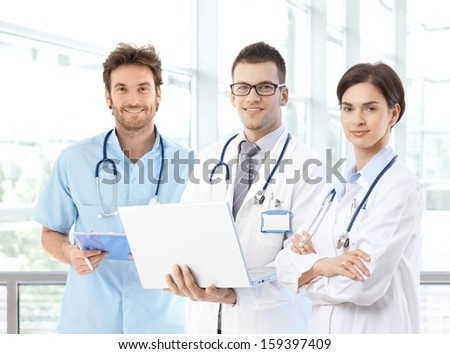 Portrait of smiling young doctors on hospital corridor looking at camera.
