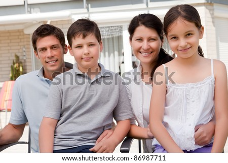Portrait of smiling young family sitting together