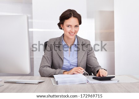Portrait Of Smiling Young Female Accountant Calculating Bills - stock photo