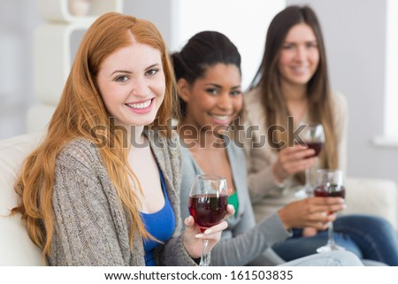 Portrait of smiling young female friends with wine glasses sitting on sofa at home
