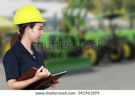 Portrait of smiling young female mechanic inspecting on a car and Tractors in auto repair shop - stock photo