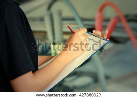 Portrait of smiling young female mechanic inspecting on a car in auto repair shop,vintage tone - stock photo