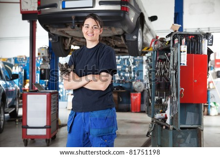 Portrait of smiling young female mechanic with arms crossed in auto repair shop - stock photo