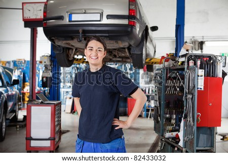 Portrait of smiling young female mechanic with hands on hips in auto repair shop