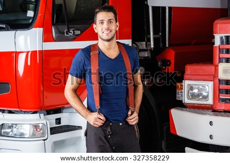 Portrait of smiling young fireman standing against firetrucks at station - stock photo