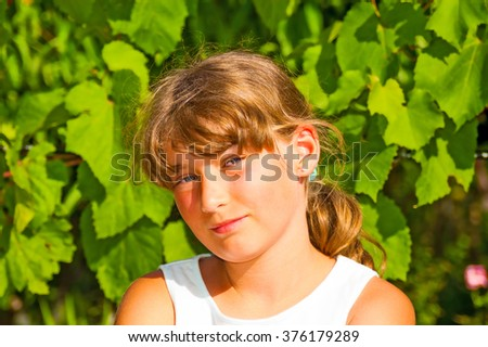 Portrait of smiling young girl in a garden - stock photo