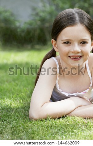 Portrait of smiling young girl lying in grass - stock photo
