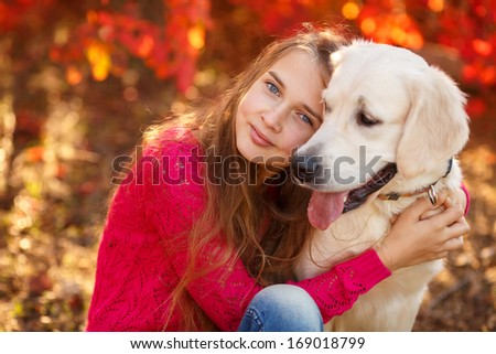 portrait of Smiling young girl posing with a labrador retriever dog out in autumn beautiful park