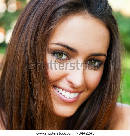 Portrait of smiling young girl sitting on grass in the forest and looking at you - stock photo