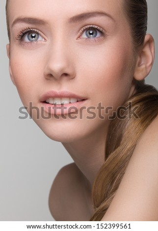 Portrait of smiling young girl with natural, beautiful lips and eyes. Studio shot on neutral background. - stock photo