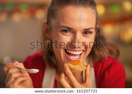 Portrait of smiling young housewife eating orange jam