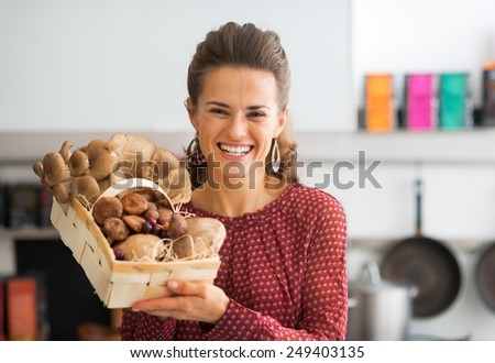 Portrait of smiling young housewife showing basket with mushrooms - stock photo