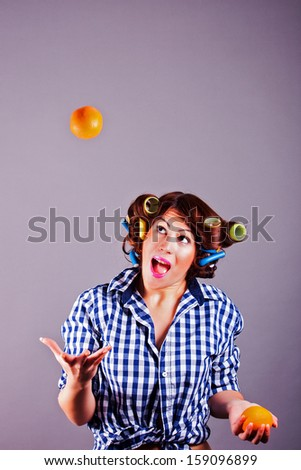 portrait of smiling young housewife with oranges - stock photo
