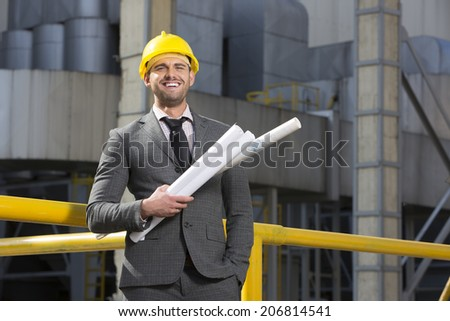 Portrait of smiling young male architect holding blueprints outside building - stock photo