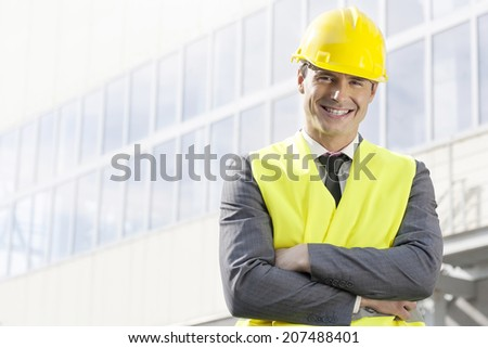 Portrait of smiling young male architect standing arms crossed outside office building - stock photo