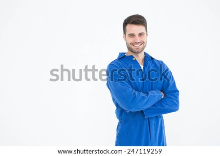 Portrait of smiling young male machanic standing arms crossed on white background - stock photo