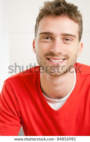 Portrait of smiling young man at home - stock photo