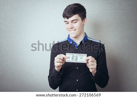 Portrait of smiling young man holding fanned US paper currency  - stock photo