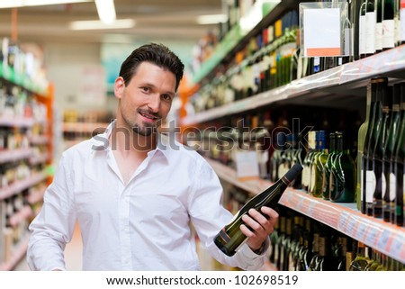 Portrait of smiling young man holding liquor bottle at supermarket - stock photo