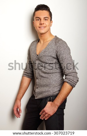 Portrait of smiling young man in gray shirt standing at the wall