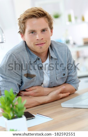 Portrait of smiling young man in office - stock photo