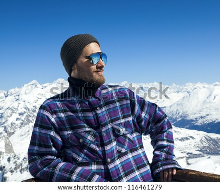 Portrait of smiling young man in sunglasses at ski resort in the background of mountains and blue sky - stock photo