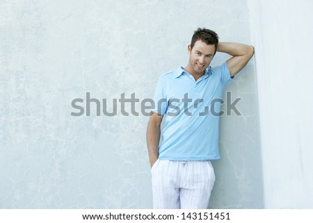 Portrait of smiling young man leaning against wall - stock photo