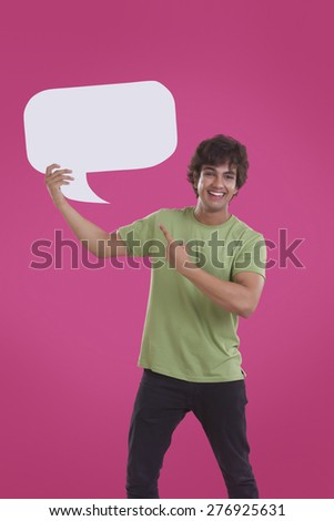 Portrait of smiling young man pointing at speech bubble over pink background - stock photo