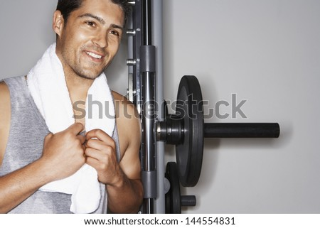 Portrait of smiling young man resting on barbell after workout at gym - stock photo