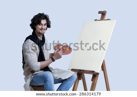 Portrait of smiling young man sitting next to easel against colored background - stock photo