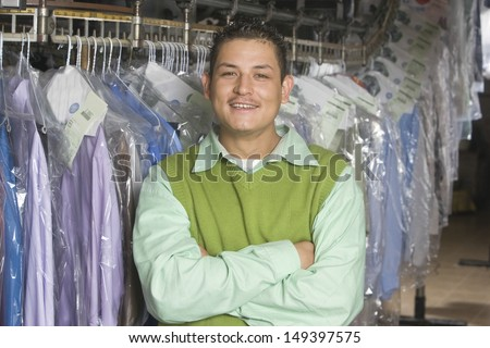 Portrait of smiling young man with arms crossed standing in front of clothes rail - stock photo