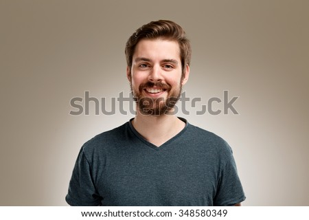 Portrait of smiling young man with beard, on neutral background - stock photo