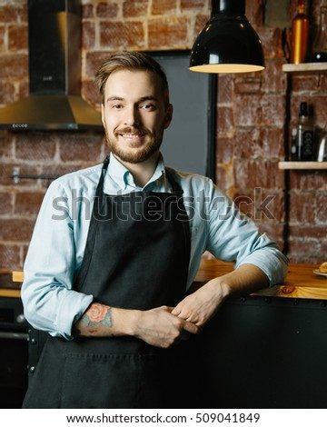 Portrait of smiling young man with facial hair wearing apron and leaning against bar counter in cafe. Blank slate board copy space for text or image.Cozy coffee shop with bartender owner staff service