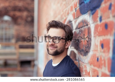 Portrait of Smiling Young Man with Facial Hair Wearing Eyeglasses and Leaning Against Brick Wall Painted with Graffiti - stock photo