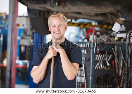 Portrait of smiling young mechanic leaning on a broom in a garage - stock photo