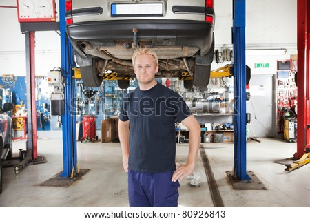 Portrait of smiling young mechanic standing inside his auto repair shop - stock photo