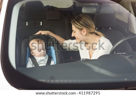 Portrait of smiling young mother looking at her child sitting in safety seat - stock photo