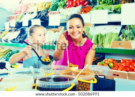 portrait of smiling young mother with daughter picking olives with spoon in food shop