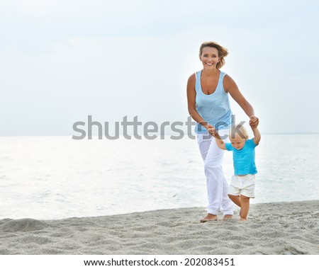 Portrait of smiling young mother with little child running on the beach. - stock photo
