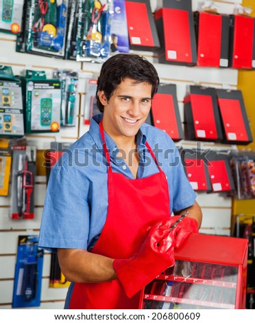 Portrait of smiling young salesman with drill bit and toolbox in hardware shop