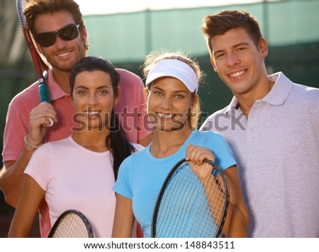 Portrait of smiling young tennis team on tennis court. - stock photo