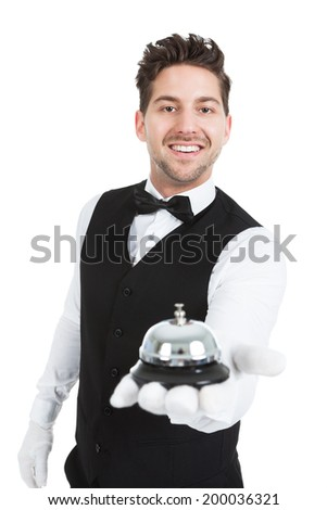 Portrait of smiling young waitperson holding service bell over white background - stock photo