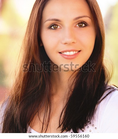 Portrait of smiling young woman against cottage.