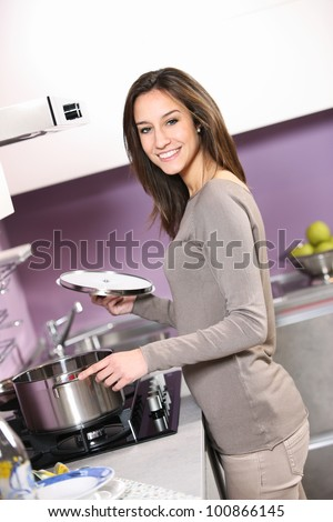 portrait of smiling young woman cooking - stock photo