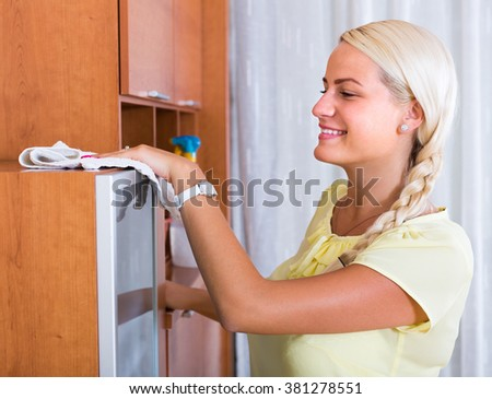 Portrait of smiling young woman dusting furniture at home