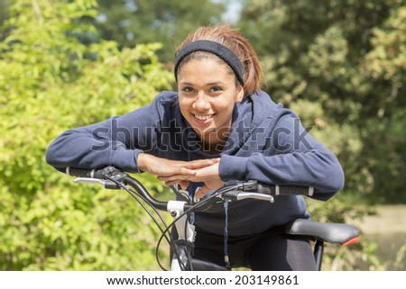Portrait of smiling young woman exercising with bicycle, outdoor.